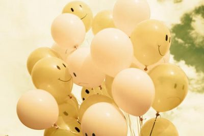 Lachende Smileys vor bewölkten Himmel in Anlehnung zum Naturheilverfahren welches psychische-, und geistige Probleme löst